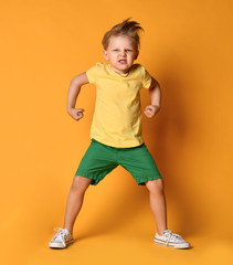 Kid boy in yellow t-shirt, green short and white sneakers is in a pose of angry monster demonstrating power and hisses with rage