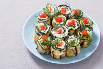 Zucchini rolls with cream cheese , tomatoes and dill