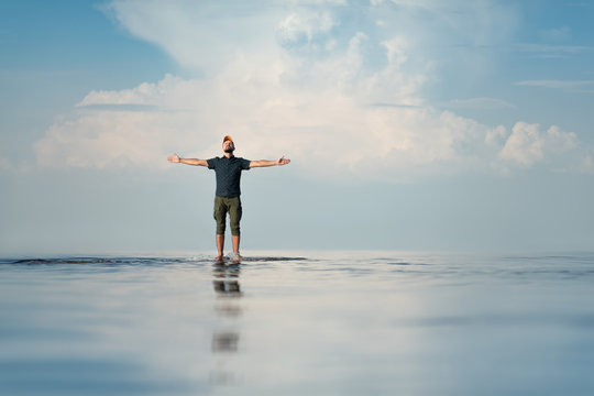 A man stands in shallow water. His hands are raised