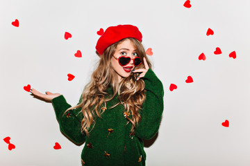 Amazing curly girl touching her sunglasses and expressing amazement in valentine's day. Studio shot of surprised european woman in green sweater isolated on white background.