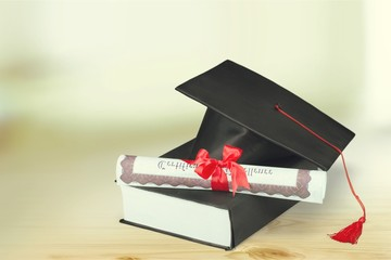 Graduation hat with book and diploma on wooden desk