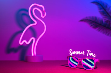 Summer time with flamingo,palm leaf,sunglasses refection neon pink and blue and green light on table with copy space.Trendy vacation holiday background.