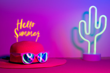 Hello Summer with hat and sunglasses refection neon light with cactus on  pink and blue light on table with copy space.Trendy vacation holiday background.