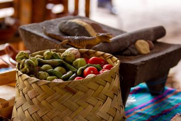 a mexican handmade basket with green tomato, chila and several ingredients for mexican food, metate