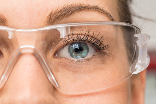 A beautiful young Caucasian is viewed closeup in the workplace, wearing protective goggles over her eyes. Pretty eyelashes and blue eyelashes seen in detail behind plastic eyewear.