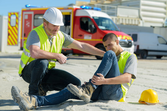 injured lying worker at work being assisted