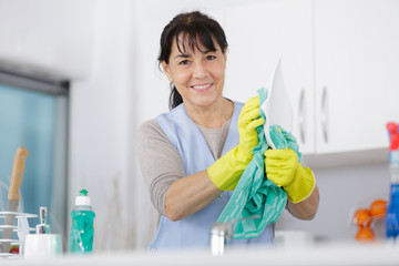 mature woman with gloves washing dishes