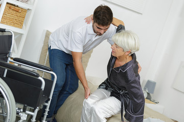 home caregiver helping senior woman getting up