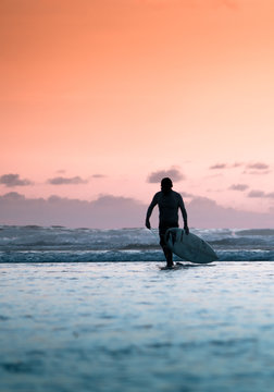 Silhouette of a surfer guy leaving the sea with his board in the sunset