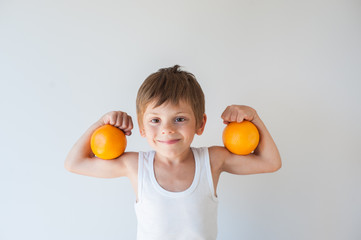 cute healthy small caucasian kid in white tank top holding two orange fruits on his biceps muscle