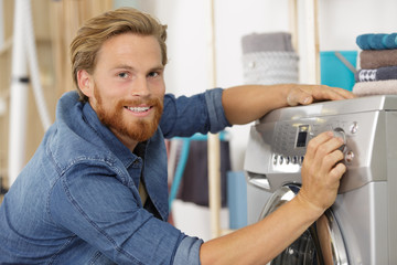man loading clothes into washing machine in kitchen