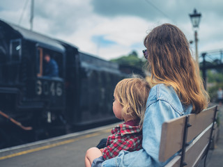 Young mother and toddler on bench watching steam train arrive