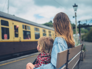 Young mother and toddler on bench watching train arrive