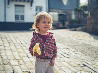 Little toddler eating banana outdoors