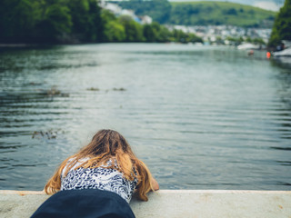 Young woman lying by river and looking at water