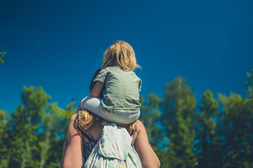 Little toddler riding on his mother's shoulders outdoors