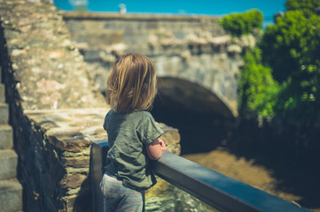 Little toddler standing by bridge