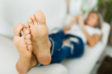 Bare feet of woman in jeans using smart phone.bare foot