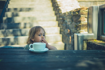 Little toddler drinking from coffee cup outdoors