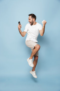 Photo of positive caucasian man in casual white t-shirt rejoicing while holding credit card and smartphone
