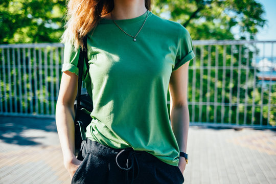 Stylish young woman standing at sunny green street