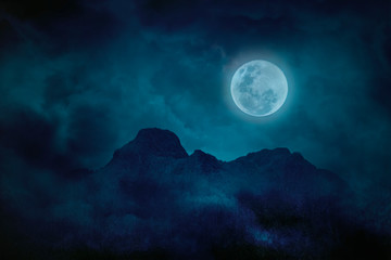 Blue full moon with mountains and forests in the darkness, Natural scary background