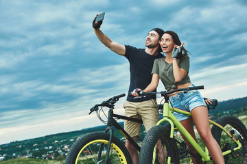 Happy couple with bicycle taking selfie by smartphone outdoors
