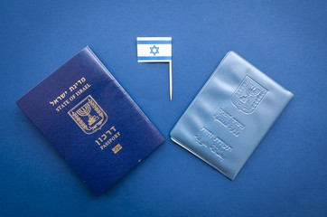 Israeli official documents: passport of Israel and national ID document on a dark blue background with a small flag of Israel. Israel citizenship concept