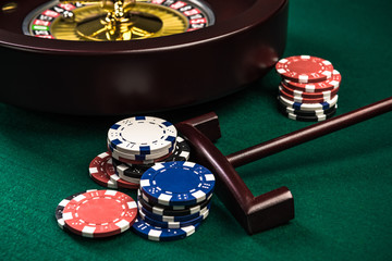 Wooden Roulette with Casino Chips on Green Felt