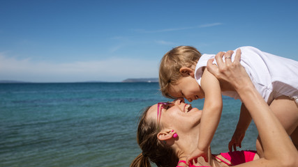 Young mother playing with her daughter by the sea