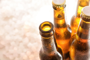 Four bottles of beer with one open on crushed ice