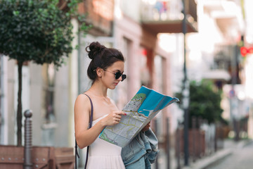 beautiful caucasian tourist woman looking at the map on the street of city