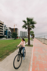 woman cyclist riding a bike on bike path on the embankment