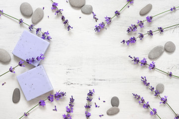 Lavender soap and flowers on rustic white wood