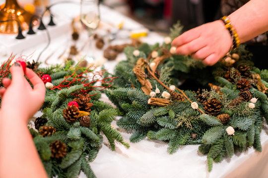 Christmas wreath weaving workshop. Woman hands decorating holida
