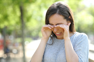 Disgusted woman rubbing her eyes in a park