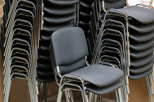 Leather and metal chairs stacked on top of each other in the mee