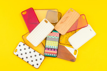 Pile of multicolored plastic back covers for mobile phones on ye