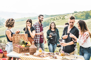 Garden Poster Tuscany Happy adult friends eating at picnic lunch in italian vineyard outdoor - Young people having fun on gastronomic weekend tuscany tour - Friendship, summer and food concept - Focus on center guys