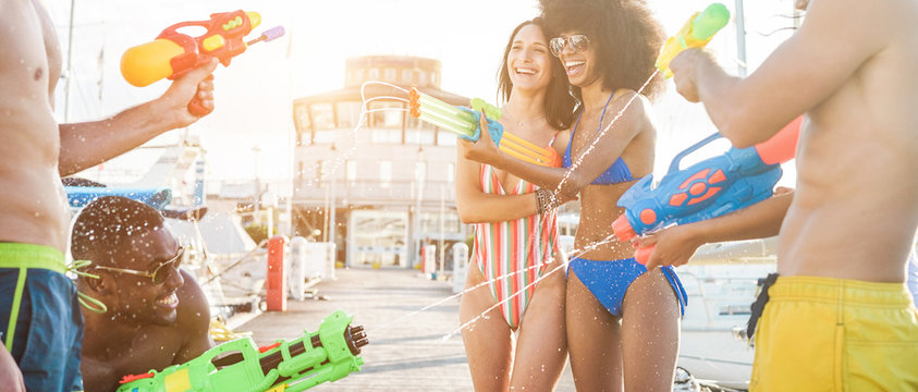 Happy friends doing battle with water guns - Young people laughing and having fun in vacation holiday - Youth, summer lifestyle and holiday concept - Focus on right women faces