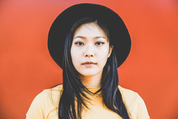 Portrait of asian girl posing with coral background - Young chinese woman in front of the camera - Fashion, casual clothes and millennial generation concept - Focus on face