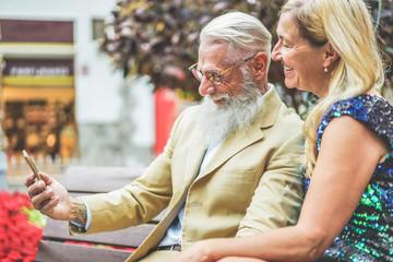 Happy senior couple having fun using smartphone app - Mature people using new trends technology - Joyful elderly lifestyle and love concept - Focus on hipster man face Fotoväggar