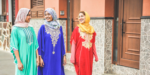 Photo sur Plexiglas Maroc Happy arabic friends walking in city center with traditional islamic clothes - Young arabian women having fun together - Friendship, youth, ethnic culture and religion concept - Focus on people