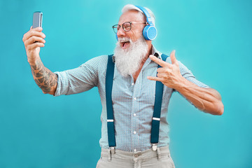 Senior hipster man using smartphone app for creating playlist with rock music - Trendy tattoo guy having fun with mobile phone technology - Tech and joyful elderly lifestyle concept - Focus on face Fototapete
