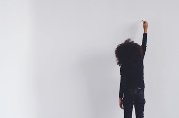 A dark-skinned girl is standing draws on a white wall.