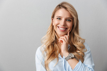 Young pretty blonde business woman posing isolated over grey wall background. Wall mural