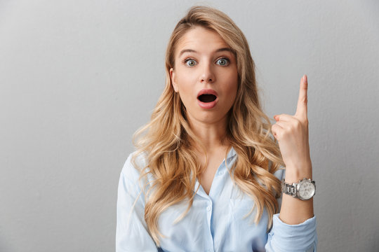 Pretty blonde business woman posing isolated shocked excited grey wall background.
