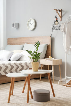 Table with plant in pot in interior of bedroom