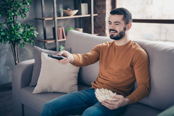 Portrait of his he nice-looking attractive bearded cheerful cheery guy spending spare time changing channels finding sports at industrial loft interior style living-room indoors