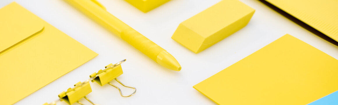 panoramic shot of yellow pen, paper clips, eraser, stickers and envelope on white background